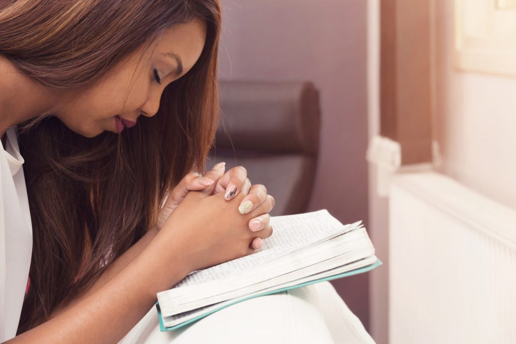 Girl Praying With her Hands Folded On The Bible
