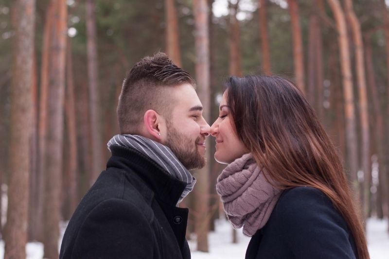 a loving couple in winter park with pine trees